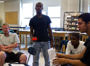 "Led by instructor Tory Bullock (standing), summer school students participated in a spoken word poetry exercise at Boston Arts Academy. ""It was very, very difficult to get kids to really participate in the beginning,'' Bullock said, though some did open up. (Kayana Szymczak for The Boston Globe)"