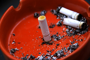 red ashtray with cigarette butts