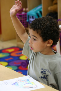 1st or 2nd grade student with his hand raised