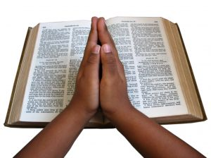 hands in prayer and bible